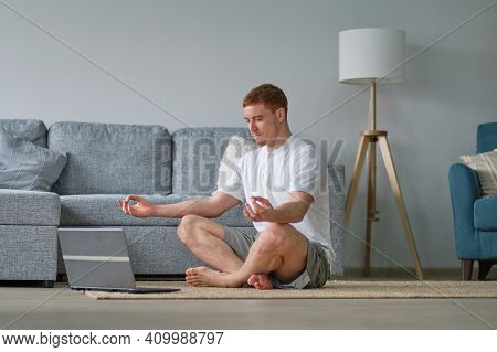Oung Cheerful Man Doing Morning Gymnastic At Home, Sitting On Yoga Mat And Stretching, Copy Space. T