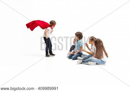 Safety. Child Pretending To Be A Superhero With His Friends Sitting Around Him. Kids Excited And Ins