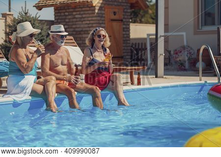 Group Of Cheerful Senior People Relaxing And Sunbathing By The Swimming Pool While On A Summer Vacat