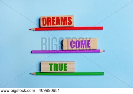 On A Blue Background, Three Colored Pencils, Three Wooden Blocks With Text Dreams Come True