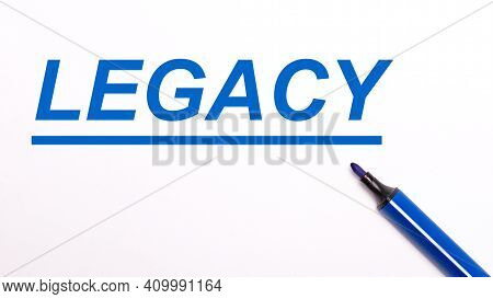 On A Light Background, An Open Blue Felt-tip Pen And The Text Legacy