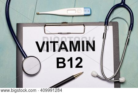 On A Light Blue Wooden Background, There Is A Paper Labeled Vitamin B12, A Stethoscope, An Electroni
