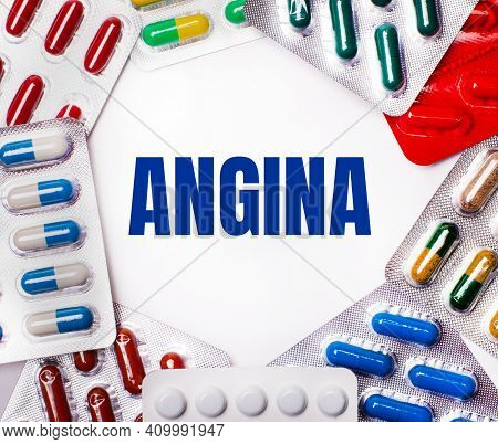 The Word Angina Is Written On A Light Background Surrounded By Multi-colored Packages With Pills. Me