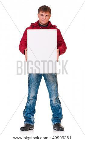 Full length portrait of a young man in winter clothing with empty white board isolated on white background