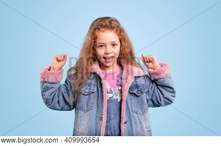 Happy Cute Little Girl In Trendy Warm Denim Jacket Keeping Fists Up While Having Good Luck And Celeb