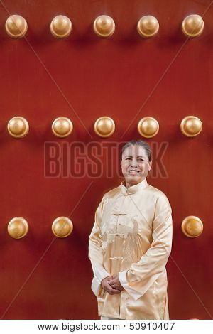 Mature woman in traditional clothes standing next to traditional Chinese door