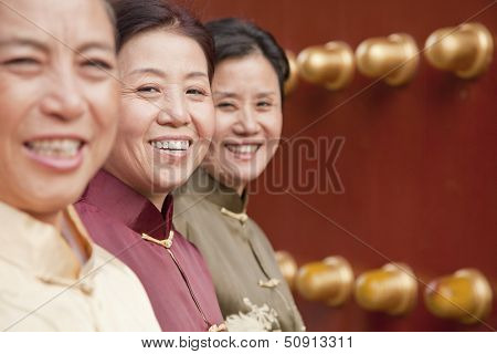 Group of mature women in traditional clothes standing next to the traditional Chinese door