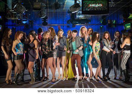 Nineteen young people having fun and dancing on a dancefloor