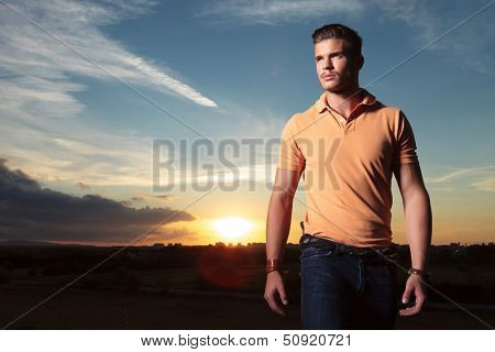 young casual man outdoor looking up, away from the camera, with the sunset behind him