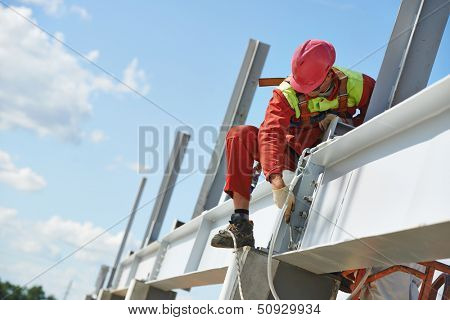 worker in uniform and safety protective equipment at metal construction frames installation and assemblage