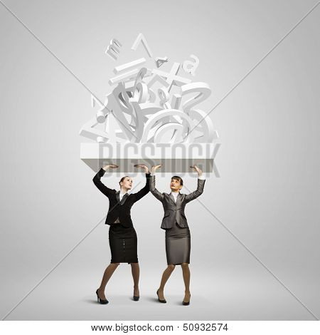 Image of two businesswomen holding burden above head