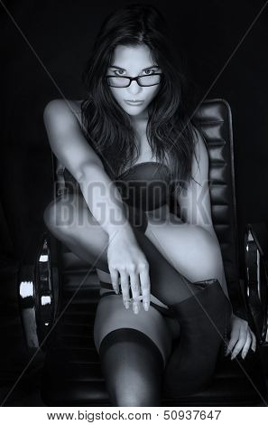 Art photo of beautiful young woman in lingerie sitting on office chair