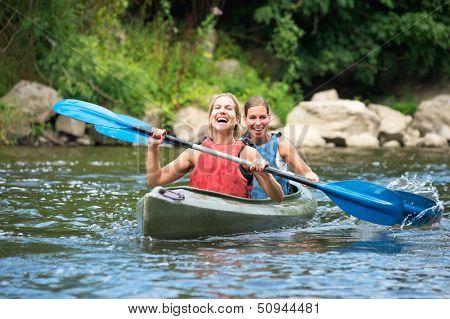 Zwei junge Frauen, Kajak einer flussabwärts lächelnd