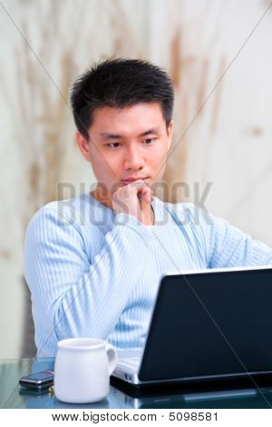 Young Chinese Man Thinking In Front Of His Laptop