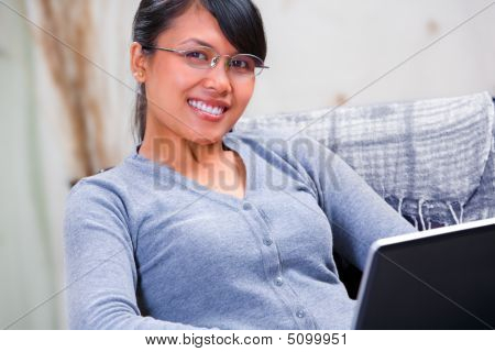 Young Smiling Woman With Laptop At Home