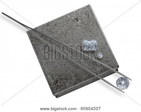 various cut cluster of diamonds and tweezers on a working jeweler anvil