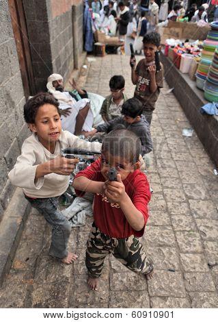 SANAA, YEMEN - MARCH 22, 2012: Children playing with toy guns on the street of Sanaa