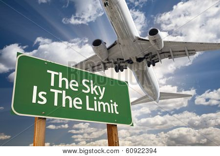 The Sky Is The Limit Green Road Sign and Airplane Above with Dramatic Blue Sky and Clouds.