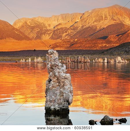 Orange sunset. The magic of Mono Lake. Outliers - calcareous tufa formation  on the smooth water of the lake