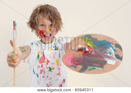 boy painting with brush and palete