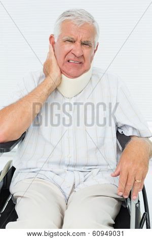 Portrait of a senior man sitting in wheelchair with cervical collar at the medical office