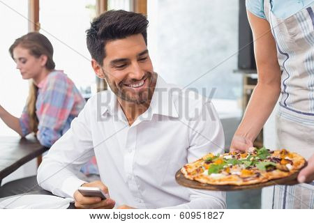 Waitress giving pizza to a smiling young man at the coffee shop