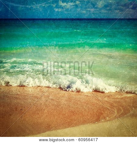 Vintage retro hipster style travel image of beautiful beach and  waves of Caribbean Sea with grunge texture overlaid
