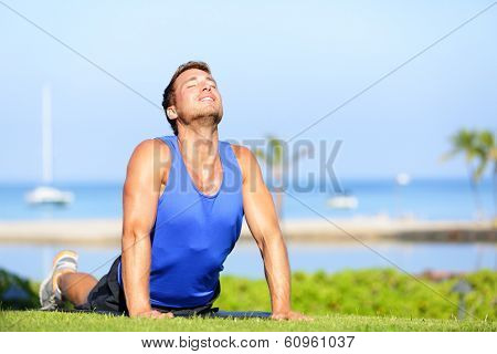 Fitness yoga man in cobra pose stretching abs stomach muscles. Fit male sports model doing stretching exercise outdoor in summer on grass. Handsome young male sports instructor.