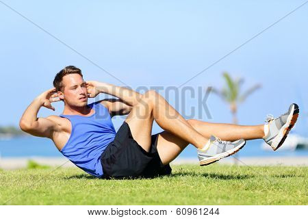 Sit ups - fitness man exercising sit up outside in grass in summer. Fit male athlete working out cross training in summer. Caucasian muscular sports model in his 20s.