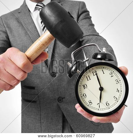 a man wearing a suit broking an alarm clock with a hammer