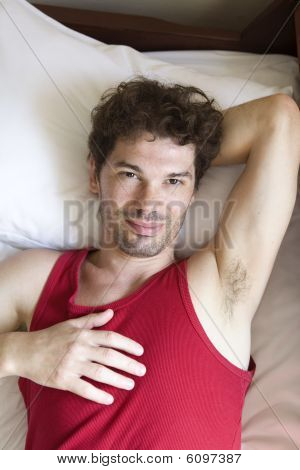serious man lying on bed