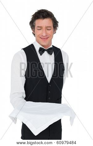 Smiling waiter looking at tray while standing over white background