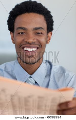 Afro-american Businessman With A Newspaper Smiling At The Camera