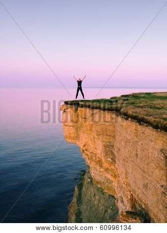 young man jumping on the cliff with spreaded hands