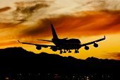 Commercial aircraft land at an airport at sunset poster