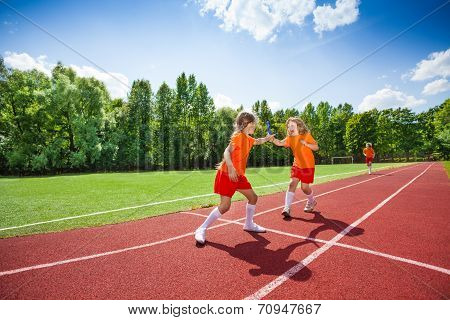 Girl with baton runs and hands it to other runner