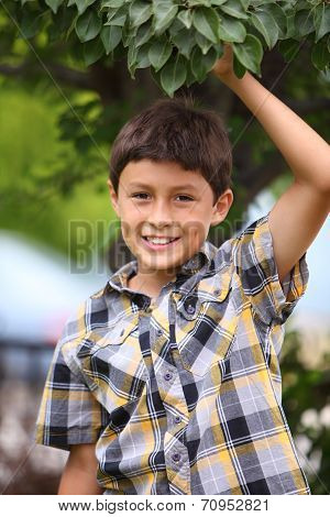 Young smiling boy under a tree