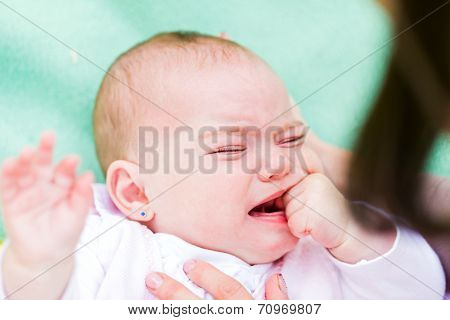 Portrait of a crying baby because she is teething poster