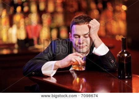 Young drunk man drinking whiskey