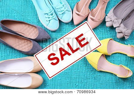 Concept of discount. Female fashion shoes on blue carpet
