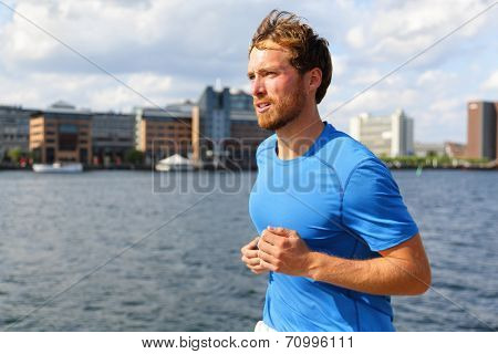 Man running in Copenhagen city. Danish male runner jogging in Bryggen, Copenhagen, Denmark. poster