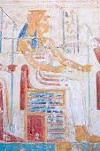 An Ancient Egyptian carved hieroglyphic painting of the goddess Mut.  One of the symbolic mothers of the king, she is shown with a vulture headdress.  Wall of the Temple of Ramses II, Abydos, Egypt. poster