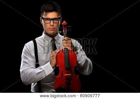 Young musician posing with a violin on black background