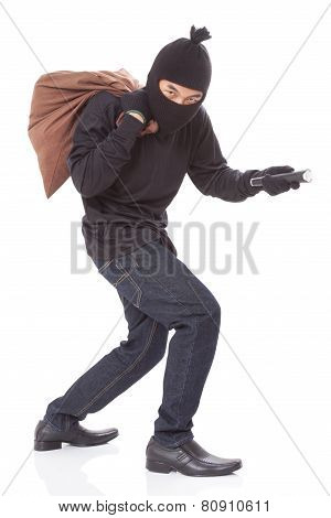 Thief with bag and holding flashlight
