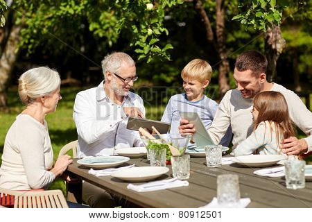family, generation, technology, home and people concept - happy family with tablet pc computers sitting at table in summer garden