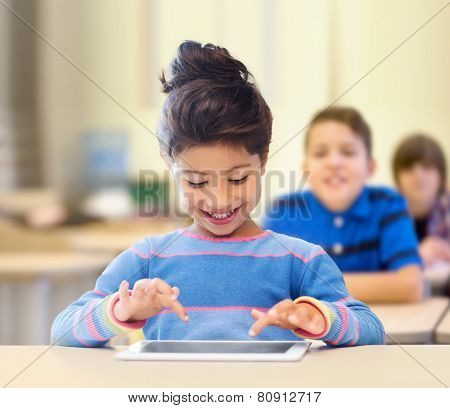 education, elementary school, technology and children concept - happy little student girl with tablet pc over classroom and classmates background