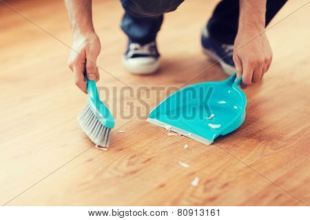 cleaning and home concept - close up of male brooming wooden floor with small whisk broom and dustpan poster