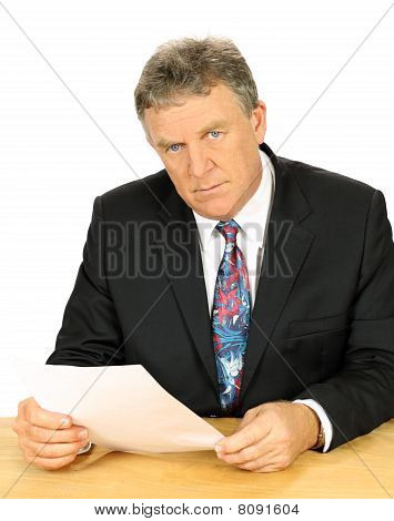 Resolute middle aged businessman with a steely glare sitting at desk. poster