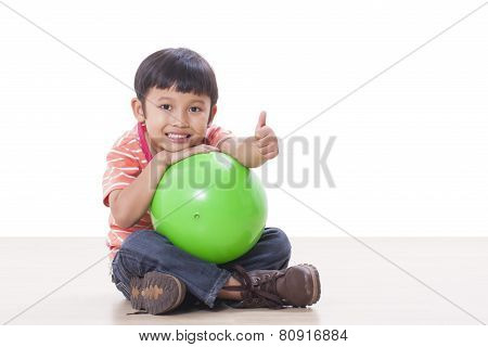 Cute little boy playing green ball
