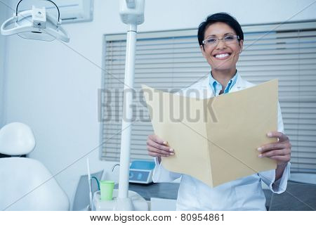 Portrait of smiling female dentist reading reports